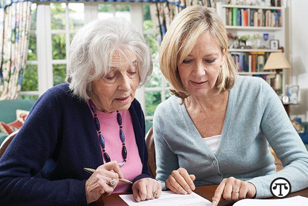 Female Neighbor Helping Senior Woman To Complete Form